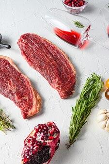 Picanha ekologiczne steki wołowe z rozmarynem, pieprzem, granatem, w pobliżu czerwonego wina w okularach i butelce na białym tle z teksturą, widok z boku.