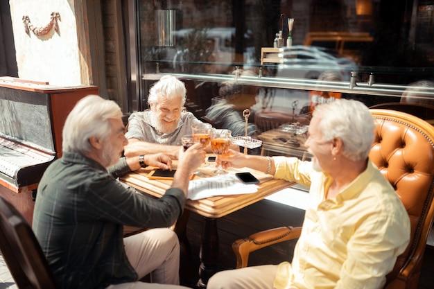 Picie alkoholu. trzech emerytów celebrujących spotkanie i pijących alkohol siedzących na zewnątrz