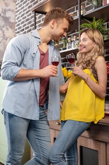 Picie czerwonego wina. młoda kochająca młoda para w dżinsach, pijąca czerwone wino w kuchni