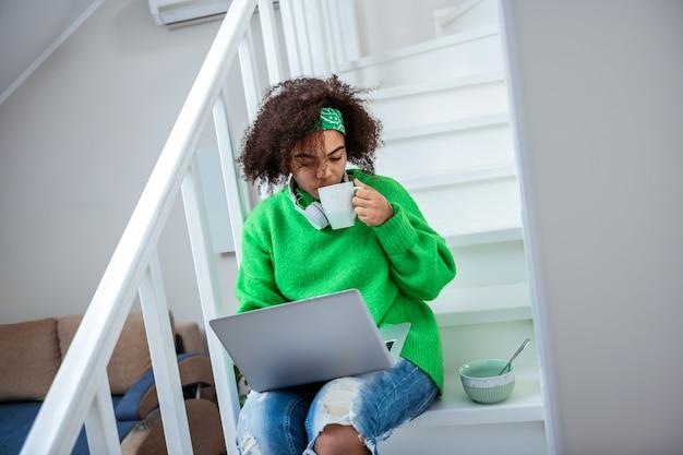 Picie gorącej herbaty. krótkowłosa młoda dama spędzająca czas w swoim domu podczas pracy z laptopem na schodach