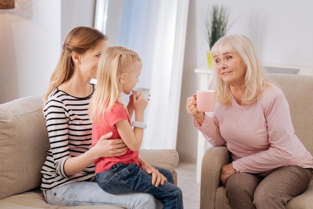 Picie herbaty. miła zachwycona, troskliwa babcia siedząca w fotelu i pijąca herbatę podczas rozmowy z wnuczką