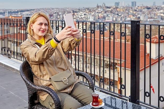 Picie herbaty na dachu hotelu z widokiem na panoramę stambułu, młoda europejka robi sobie zdjęcia lub robi selfie za pomocą smartfona.