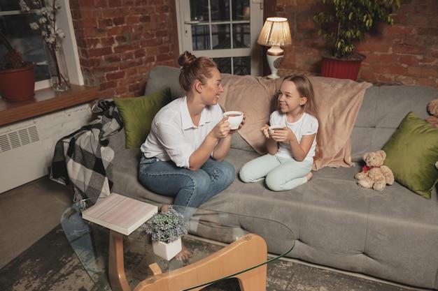 Picie herbaty, rozmawianie. matka i córka podczas samoizolacji w domu na kwarantannie, czas rodzinny przytulnie, komfort, życie domowe. wesołe, szczęśliwe uśmiechnięte modelki. bezpieczeństwo, zapobieganie, koncepcja miłości.