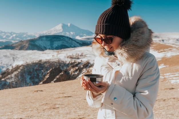 Picie herbaty w górach. podróżnik z kubkiem gorącego napoju w górach.