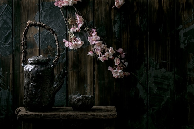 Picie herbaty wabi sabi ceramiczny kubek w stylu japońskim z ciemnej gliny i imbryk z kwitnącymi gałęziami wiśni. ciemna ściana drewniana. skopiuj miejsce