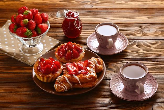 Picie herbaty z tartaletkami i ciastka z truskawkami