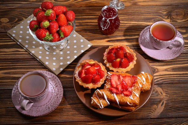 Picie herbaty z tartletami i ciastami z truskawkami