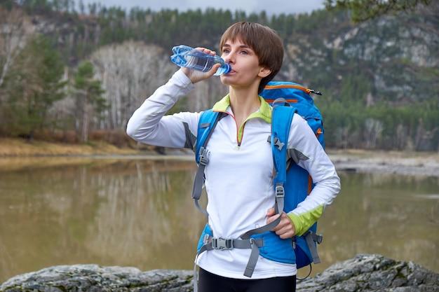 Picie hikikng kobieta z butelką wody i plecak. portret sportów na świeżym powietrzu