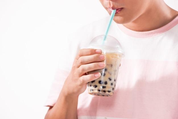 Picie jasnobrązowej kremowej herbaty bąbelkowej i czarnych pereł tapioki w plastikowych kubkach na stole.