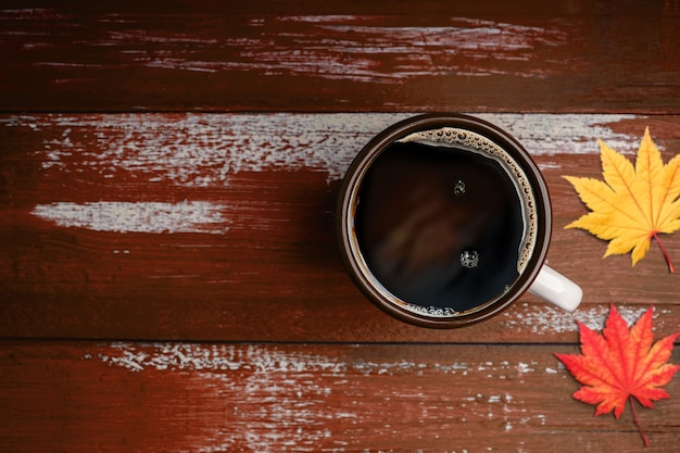 Picie kawy w okresie jesienno-jesiennym. filiżanka gorącej kawy na pomarańczowy brązowy drewniany stół. widok z góry. skoncentruj się na pucharze. otoczony przez rozmazany liść klonu
