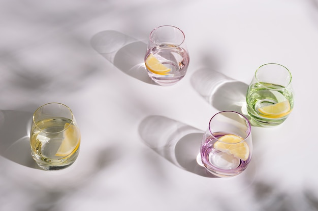 Picie naturalnej wody w kolorowych szklanych szklankach z plasterkiem cytryny na białym tle w słoneczny dzień