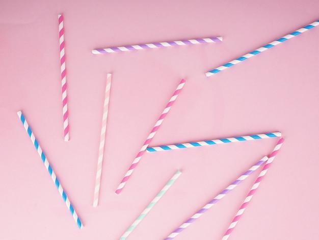 Picie papierowych słomek do koktajli na różowym tle. ekologiczne słomki jednorazowe papierowe.
