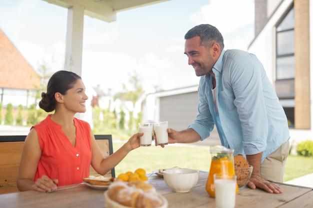 Picie porannego mleka. wesoła kochająca para pijąca mleko rano jedząca śniadanie na zewnątrz