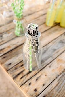 Picie słomki z papieru do picia lemoniady w szklanej butelce.