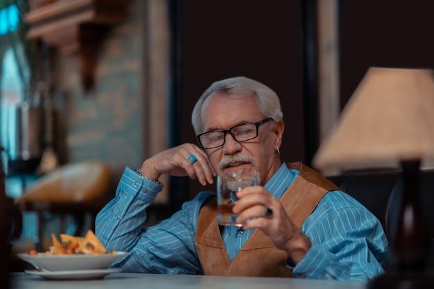 Picie whisky w samotności. siwowłosy, brodaty mężczyzna noszący pierścionek pijący whisky w samotności i myślący