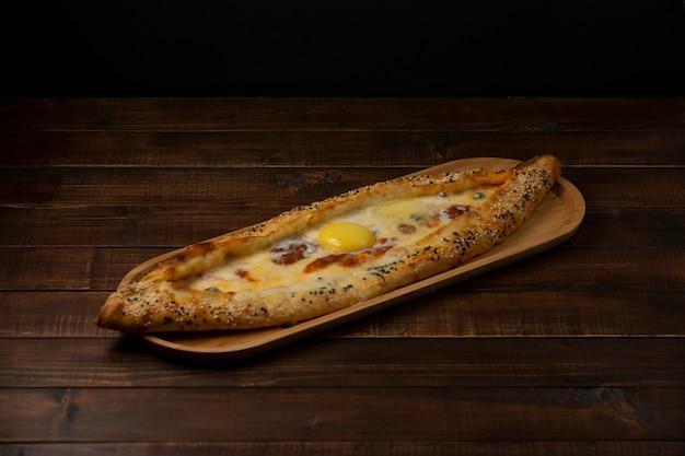 Pide z serem kiełbasianym i oliwką podawane w drewnianej desce do serwowania