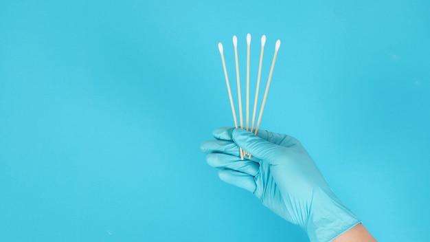 Pięć bawełnianych patyczków w ręku z niebieskimi rękawiczkami medycznymi lub lateksowymi rękawiczkami na niebieskim tle.koncepcja covid-19