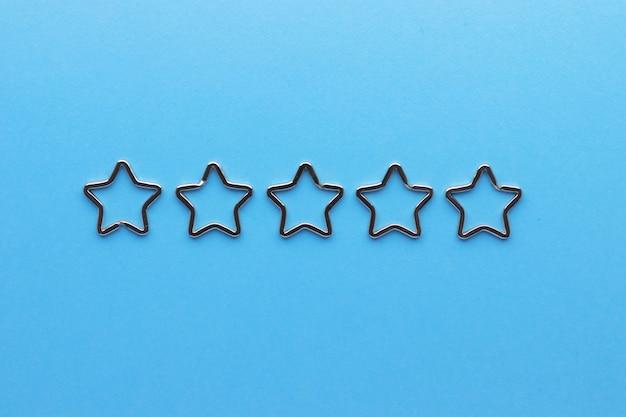 Pięć błyszczących metalowych breloków dzielonych w kształcie gwiazdy na breloki. chromowane zapięcie na brelok na niebieskim tle.