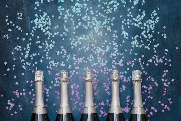 Pięć butelek szampana z holograficznymi gwiazdami konfetti na niebiesko. skopiuj miejsce, widok z góry