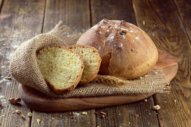 Piec chleb na drewnianym stołowym tle