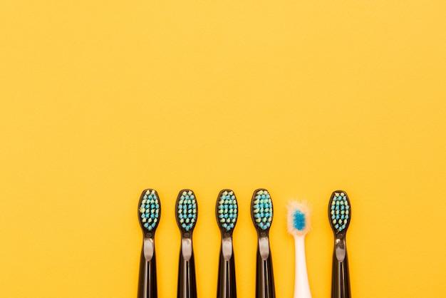 Pięć czarnych nowych szczoteczek do zębów i jedna stara biała szczoteczka do zębów na żółtym tle