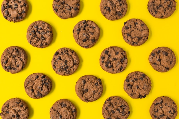 Piec czekoladowi ciastka na żółtym tle