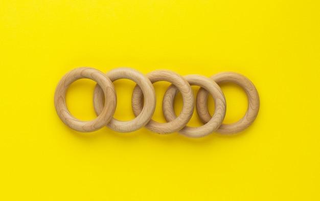 Pięć drewnianych pierścieni na żółtym tle. gryzak dla niemowląt z naturalnego drewna. ekologiczna zabawka dla dzieci. widok z góry, płaski układ z miejscem na kopię.
