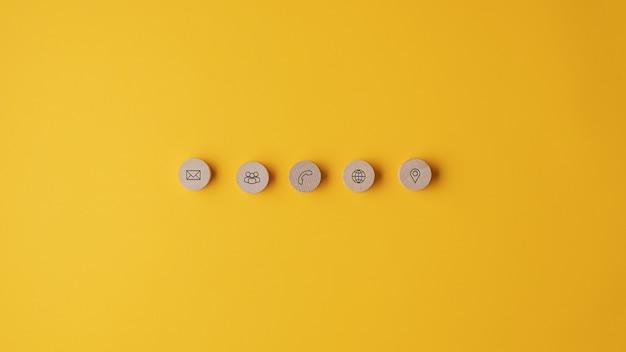 Pięć drewnianych, wyciętych okręgów z ikonami kontaktu i informacji umieszczonymi w rzędzie
