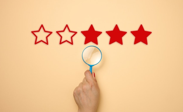 Pięć gwiazdek i ręka z niebieską plastikową lupą na beżowym tle. ocena jakości usług i towarów, ocena wysoka