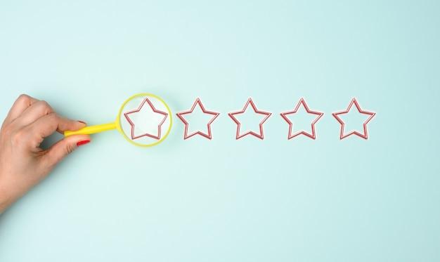 Pięć gwiazdek i ręka z żółtą plastikową lupą na niebieskim tle