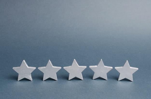 Pięć gwiazdek na szaro. sukces w biznesie. pojęcie oceny i oceny