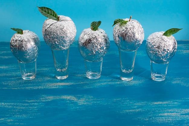 Pięć jabłek w folii z naturalnymi zielonymi liśćmi.