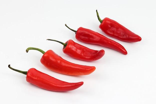 Pięć jasnoczerwonych papryki słodkiej na białym tle
