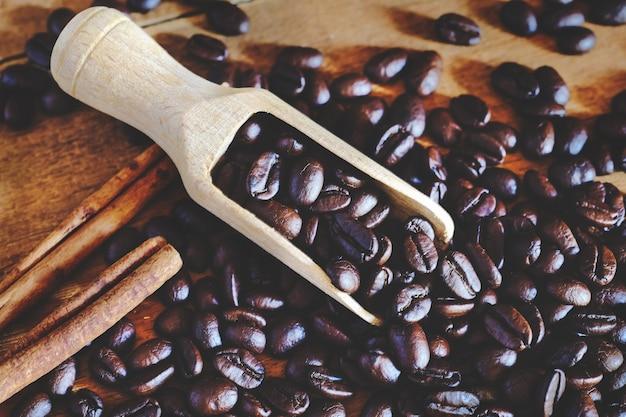 Piec kawową fasolę w drewnianej łyżce na stole.