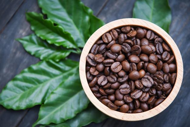Piec kawowe fasole na drewnianym pucharze z zielonym kawowym liściem na ciemnym tle