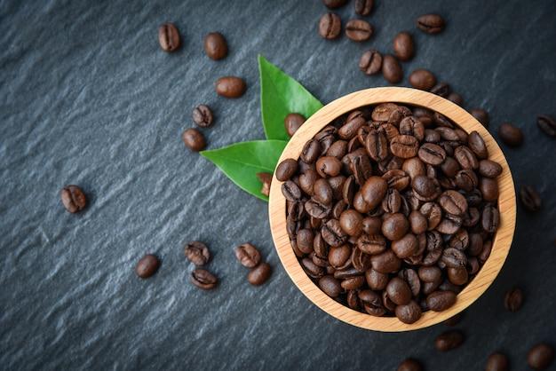 Piec kawowe fasole na drewnianym pucharze z zielonym liściem i zmrokiem - odgórny widok
