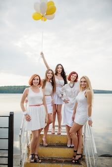 Pięć kobiet z balonami pod ręką nosiło białe sukienki na przyjęciu panieńskim na molo nad jeziorem.