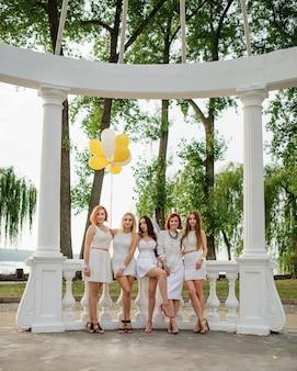 Pięć kobiet z balonami pod ręką nosiło białe sukienki na przyjęciu panieńskim na tle białych kolumn.