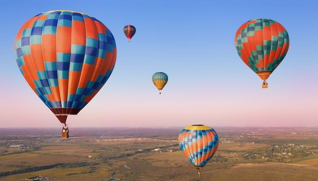 Pięć kolorowych balonów w powietrzu nad równinami.