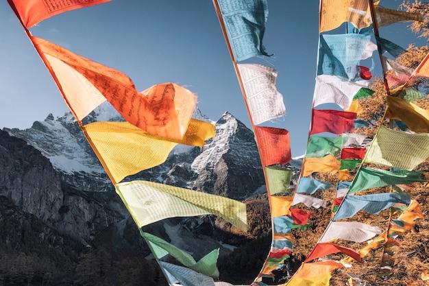 Pięć kolorowych flag modlitewnych latających z górą xiannairi w lesie jesienią. rezerwat przyrody yading