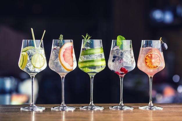 Pięć kolorowych koktajli gin z tonikiem w kieliszkach do wina na blacie barowym w psie lub restauracji.