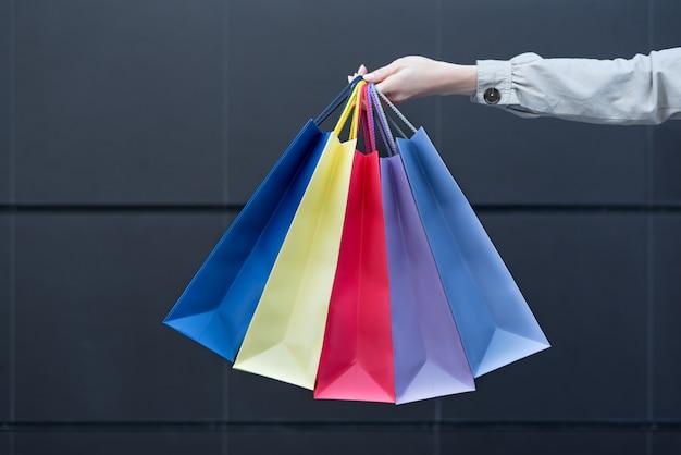 Pięć kolorowych toreb na zakupy w kobiecej dłoni.