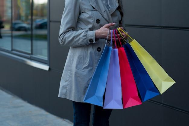 Pięć kolorowych toreb na zakupy w kobiecych rękach.