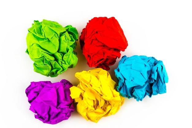 Pięć kolorowych zmiętych papierowych piłek odizolowywających na bielu