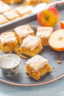 Pięć kostek ciasta jabłkowego z polewą śmietankową, obok sitko do cukru i pokrojone na pół jabłko.