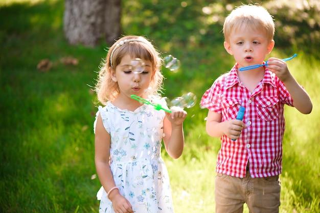 Pięć lat kaukaski dziecko dziewczynka i chłopiec dmuchający bańki mydlane na świeżym powietrzu o zachodzie słońca - szczęśliwe beztroskie dzieciństwo