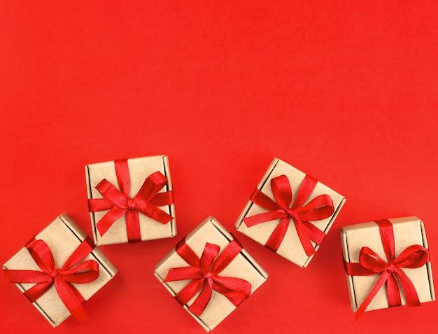 Pięć małych brązowych prezentów z czerwoną wstążką na czerwonym tle
