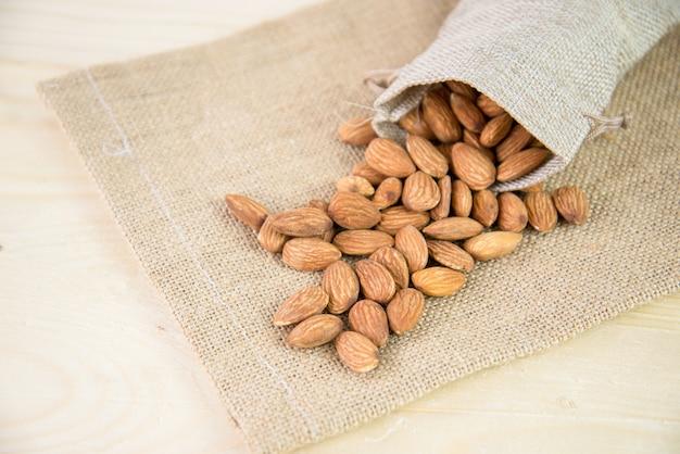 Piec migdał w burlap torbie lub workowej torbie na workowym tle. migdał to przekąska lub surowiec do gotowania. zdrowe jedzenie. niskokaloryczne lub dietetyczne jedzenie.