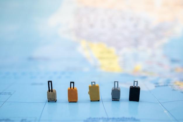 Pięć miniaturowych figur bagażu z wieloma stylami stoi na mapie świata.