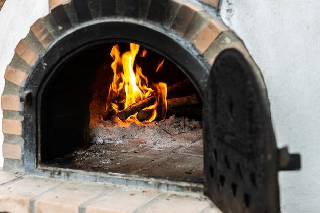 Piec na drewno artisan zbudowany na zewnątrz z otwartymi drzwiami i ogniem w środku